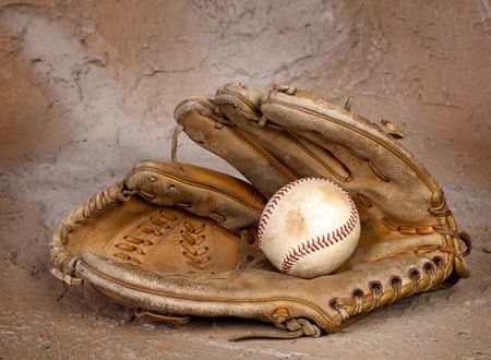 baseball glove: Old weathered baseball glove against a grungy background