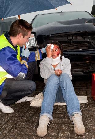 Paramedic taking care of an injured woman under an umbrella photo