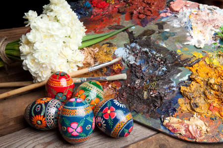 Painter's pallet with brushes and russian easter eggs photo