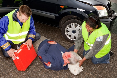 unconscious: Car crash victim being helped by paramedics (the sleeve badges have been replaced by a non existing logo)