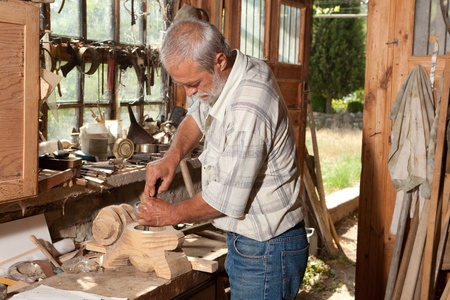 carpenter's sawdust: Old shed with a skilled carpenter working with wood Stock Photo