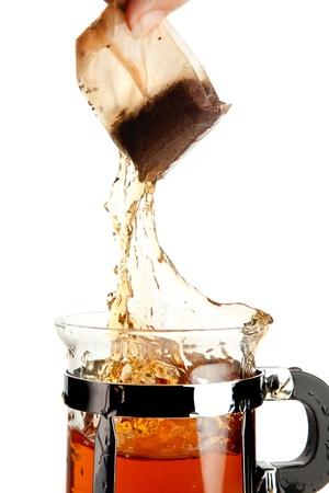 Female hand removing a tea bag with a splash photo