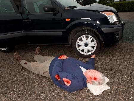 Dead or unconscious man lying next to a wrecked car Stock Photo - 12250405