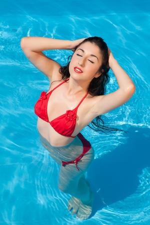 Bathing beautiful woman posing in her bikini in the swimming-pool Stock Photo - 12250401