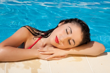 Wet hair woman relaxing at the poolside on a hot day Stock Photo - 12250402
