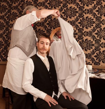coupe de cheveux homme: Barber met une cape sur son client pour une coupe de cheveux dans un salon de coiffure victorienne Banque d'images