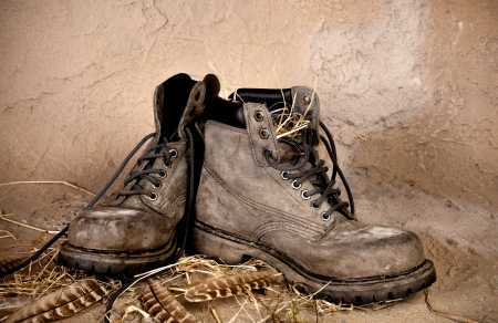old shoes: Pair of weathered old boots on a grunge background Stock Photo