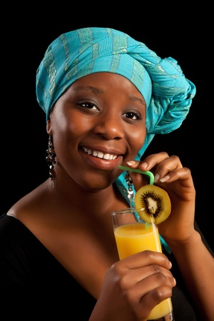 Young African lady drinking orange juice and wearing traditional ghanese scarf Stock Photo - 12250364