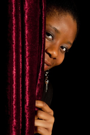 ghanese: Young African Ghanese woman hiding shy behind a curtain