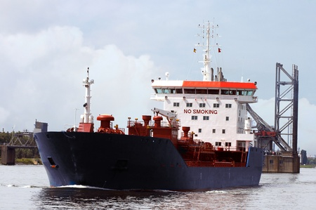 Tanker passing the entry of the docks in Antwerp harbor  photo
