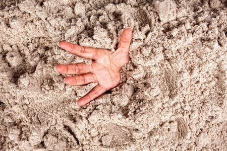 despair: Hand on a beach sinking or drowning in quicksand