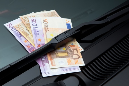 windscreen wiper: Euros stuck under a windshield wiper symbolizing car expenses Stock Photo