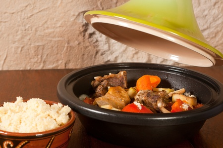 Lid being lifted of a traditional moroccan tajine dish photo