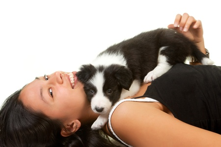 border collie puppy: Young woman playing with a 5 weeks old border collie puppy