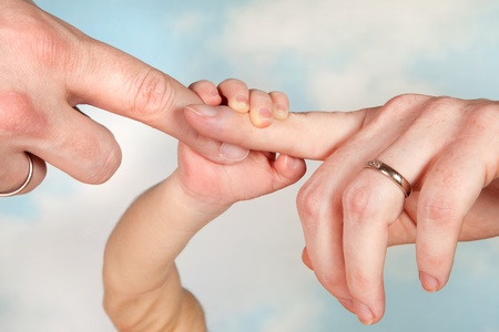 Thee hands of a baby and his parents wearing wedding rings Stock Photo - 12880179
