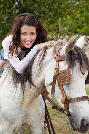 Smiling girl sitting on her favorite farm horse photo