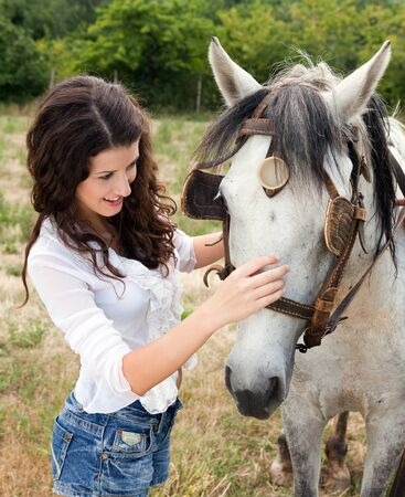 Smiling woman meeting a farm horse in a meadow photo