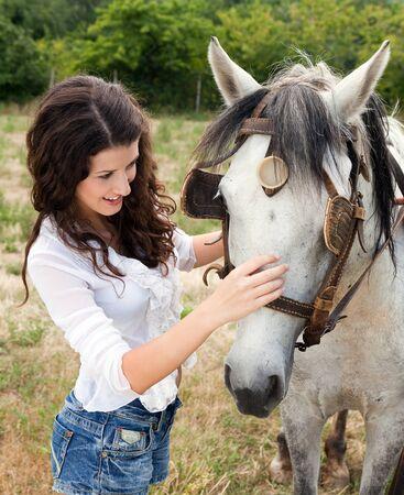 femme et cheval: Sourire, femme répond à un cheval de la ferme dans un pré