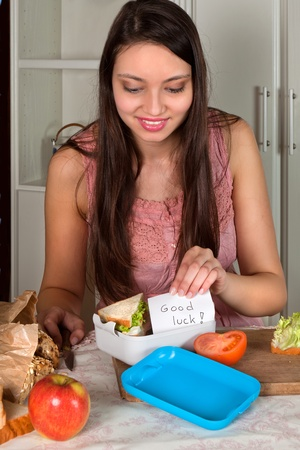 fresh graduate: Young woman putting a good luck note in a lunchbox, for a graduation or first day on a job Stock Photo
