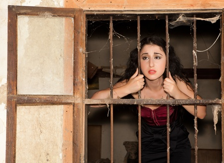 Sad woman in prison behind bars of a derelict building photo
