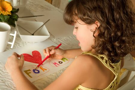 Little girl making a drawing for mothers day photo