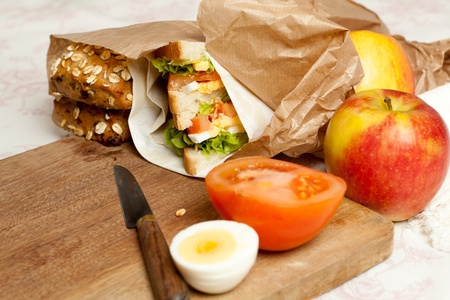 Fruit, sandwiches and buns in a brown paper lunch bag photo