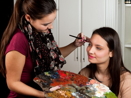 Female make-up artist working with a painters palet in her hands photo