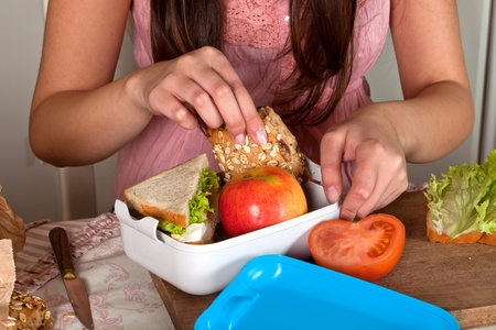 preparing: Hands of a woman preparing a lunchbox on the kitchen table Stock Photo