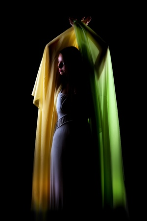 Green and yellow silky wings of voile fabric held by a young woman Stock Photo - 12999244
