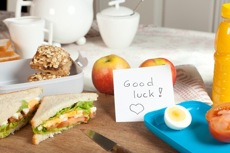 Lunchbox on breakfast table with good luck note Stock Photo - 13058075