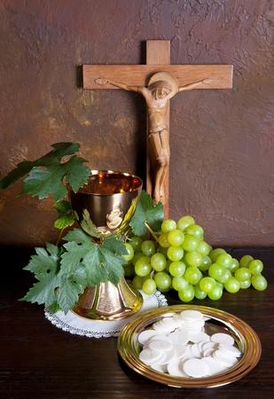 kelch: Heilige Kommunion Bild zeigt einen goldenen Kelch mit Trauben und Brot Wafern