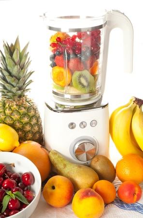 licuadora: Blender rodeado de todo tipo de fruta de verano para la toma de batido