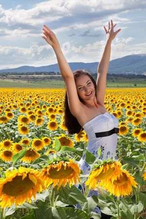 Happy young woman raising her hands in a sunflower field Stock Photo - 13142852