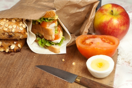 Brown paper bag with sandwich and apple for lunch photo