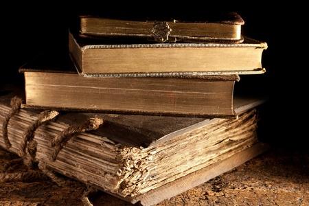 Pequeña pila de libros antiguos en el estado de weatered sucio y el oro subió Foto de archivo