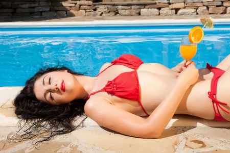 Young model having a cocktail drink at the poolside photo