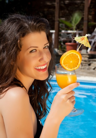 Pretty model drinking a cocktail at the poolside photo