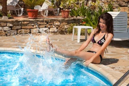 jolie pieds: Jeune femme s'amuse à le clapotis piscine avec de l'eau Banque d'images