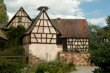 Old timbered farm houses with stork nests in Ungersheim, Alsace, France