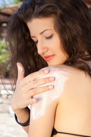 sun lotion: Attractive young woman putting sun lotion on her shoulders