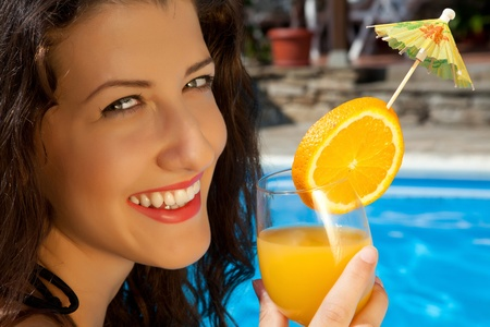 Closeup of a young woman having a cocktail at the poolside photo