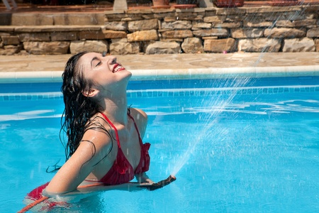 hose: Hot day and a woman in the swimming-pool is playing with the water hose