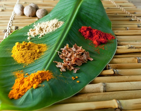 Display of colorful spices on a banana leaf like curcuma, nutmeg, pepper, currie and paprika photo