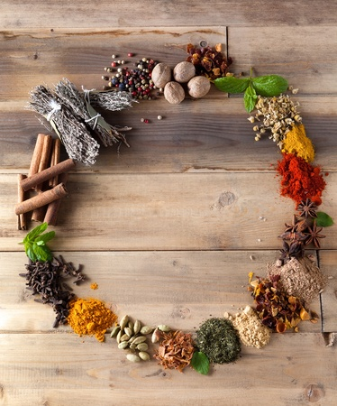 Beautiful circle of colorful spices and herbs on a wooden table photo