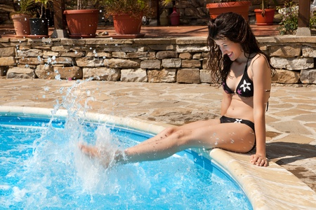 Hot summer day with a woman splashing with water at the poolside photo