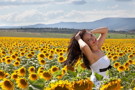 Wind in the hair of a beautiful woman in a Bulgarian summer sunflower field Stock Photo - 13563602