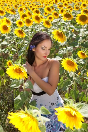 Beautiful brunette taking care of her hair in a Bulgarian sunflower field Stock Photo - 13563603