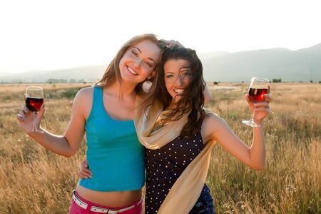 friends drinking: Happy girl friends drinking wine during the golden evening hour Stock Photo