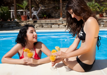 Two women chatting with orange juice drinks at the poolside photo