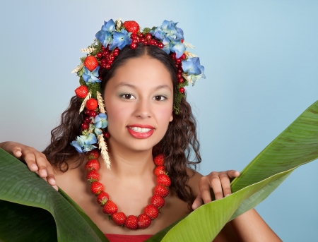 Summer woman with strawberries, fruit and flowers in her hair behind a banana plant Stock Photo - 13658605